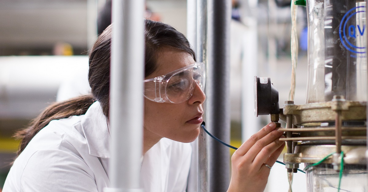 Female student in labcoat and goggles consults dial on laboratory equipment