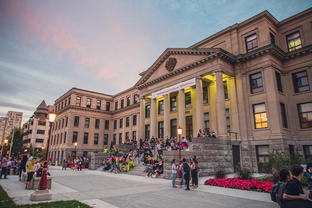Pavillon Tabaret lors du coucher de soleil, avec des étudiants assis sur les marches avant