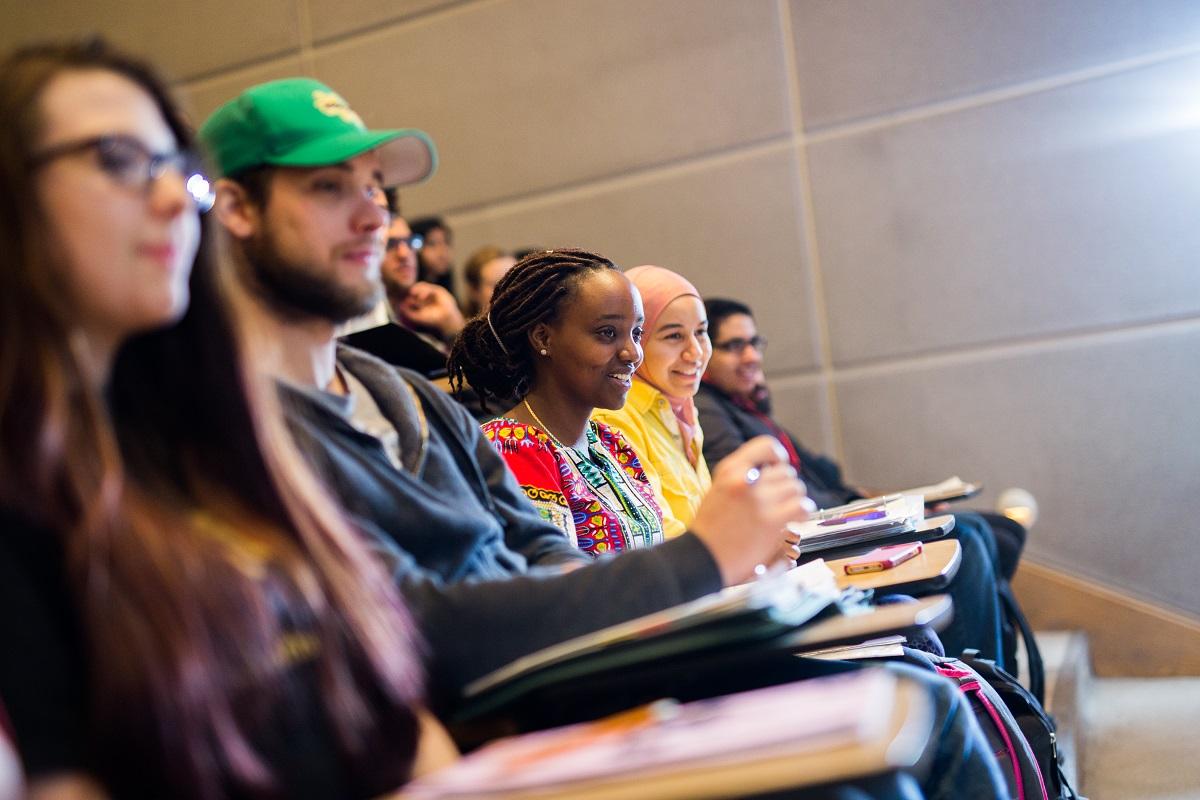 Des étudiants, en rangée, assis dans une salle de classe.