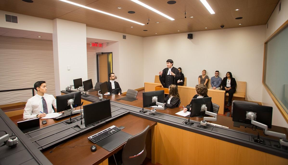 Un homme plaide sa cause devant un juge et trois autres avocats dans une salle d'audience