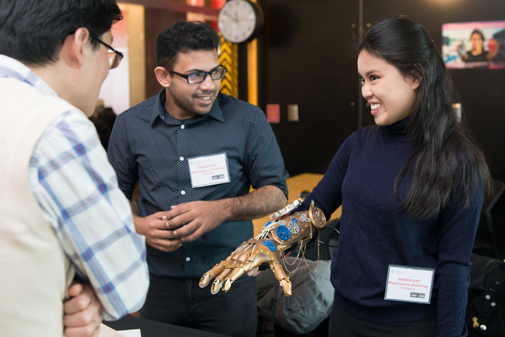 Female student presents robotic hand.