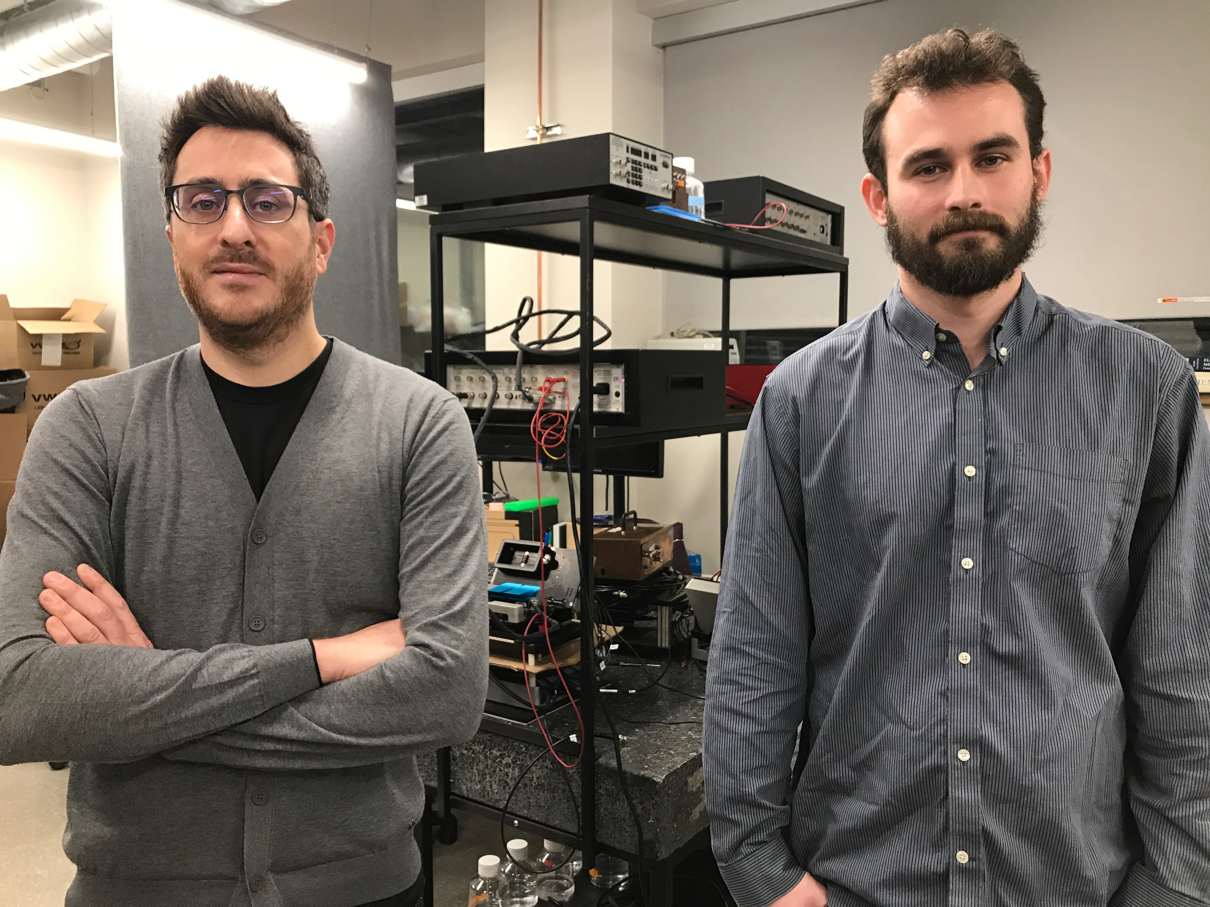Vincent Tabard-Cossa and Kyle Briggs standing in front of the device they created