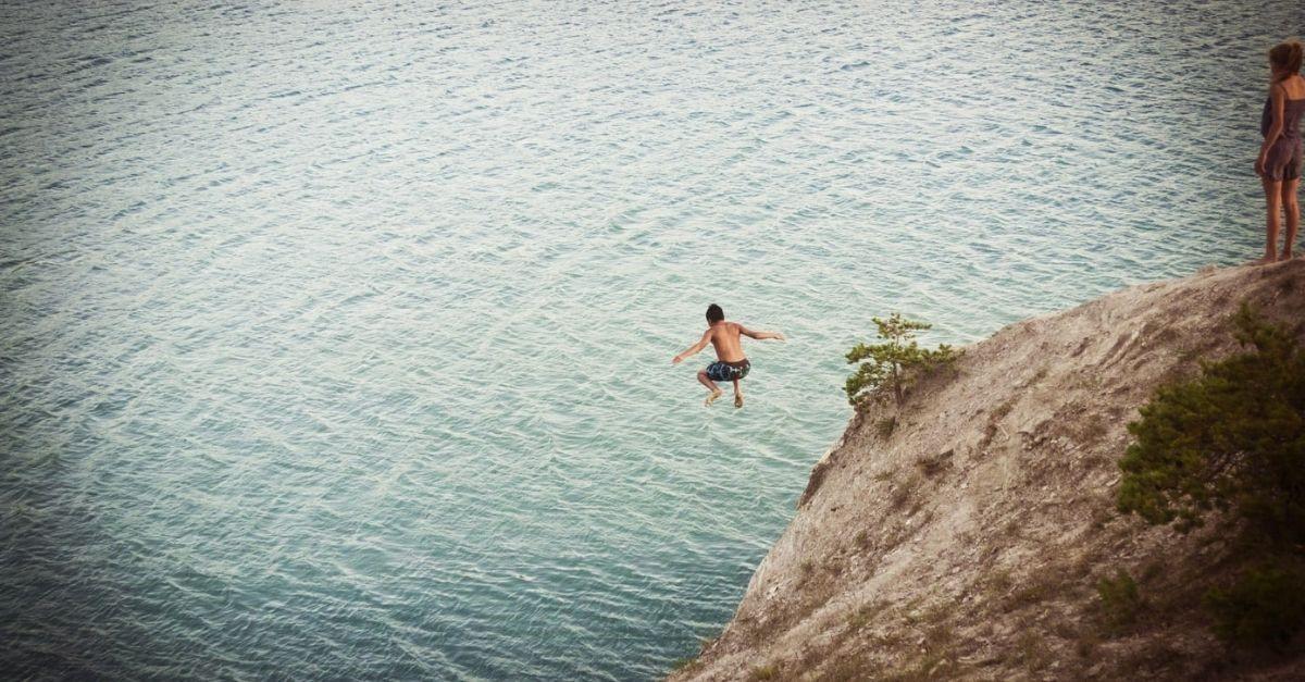 Homme sautant d'une falaise dans un plan d'eau