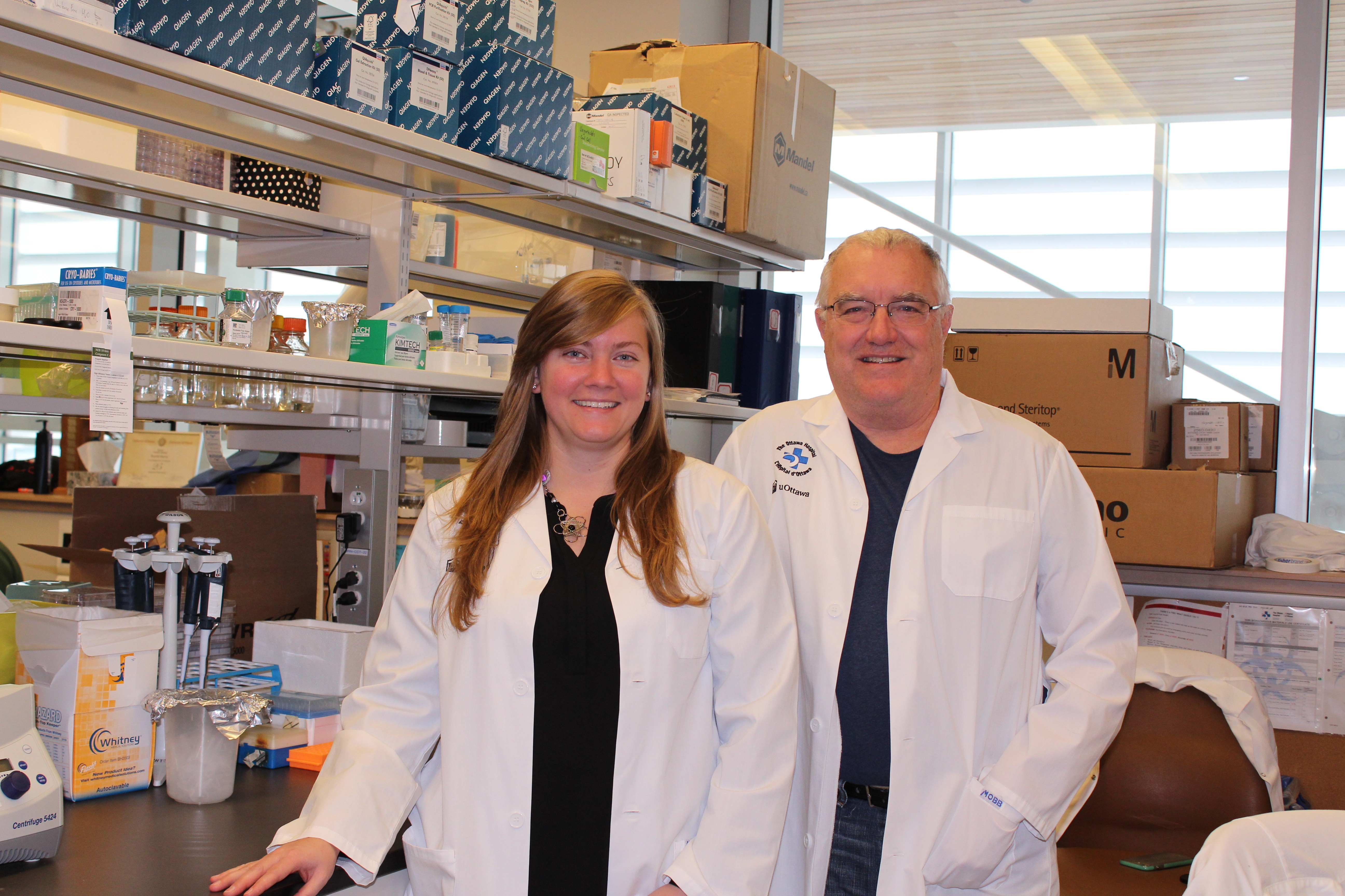 A woman and man stand, in white coats, in a research laboratory.