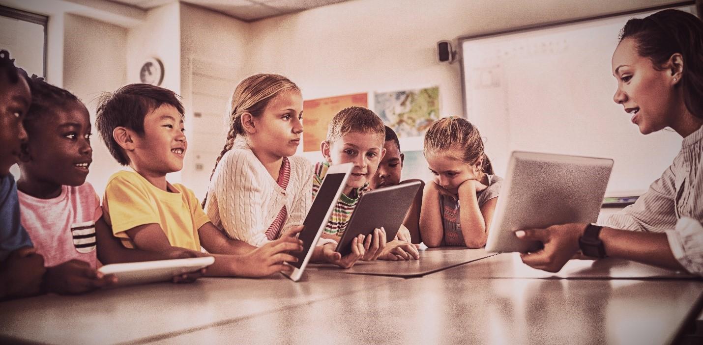 Une enseignante tient une tablette électronique devant des élèves