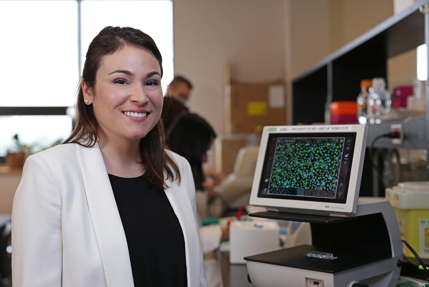 Professor Mireille Ouimet in a lab coat in front of a screen