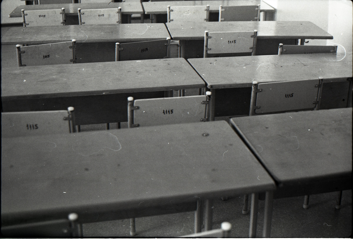 Black and white picture of empty desks and chairs in classroom.
