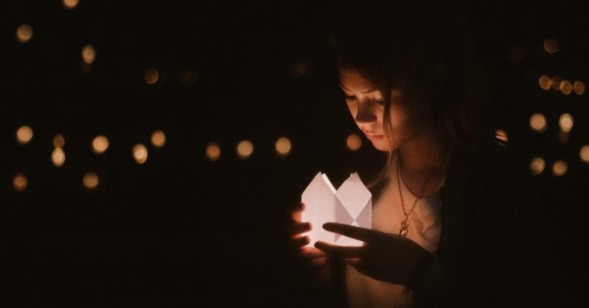 Une femme tenant une chandelle lors d'une cérémonie commémorative.