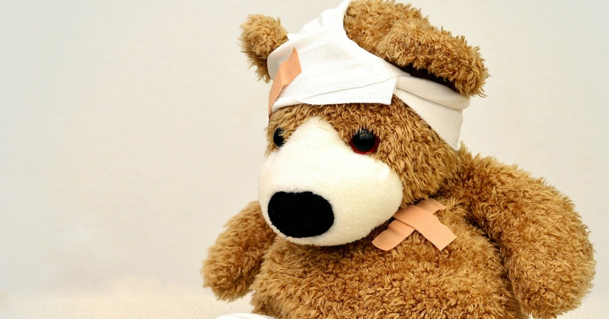 Teddy bear with a bandage on its head and on its heart