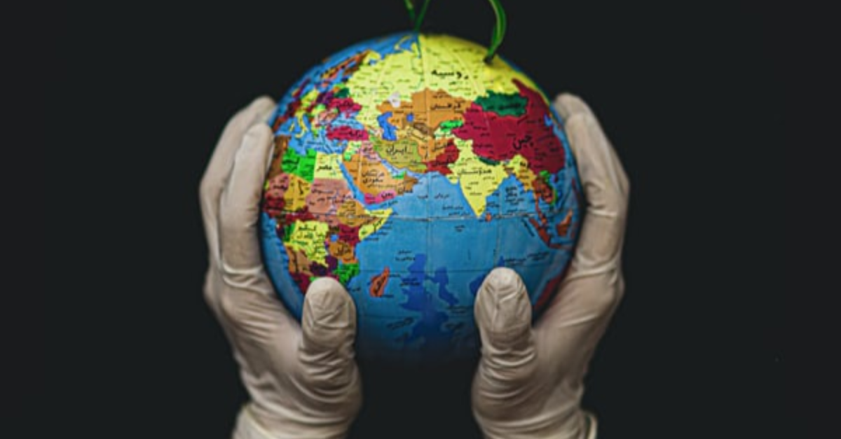 Hands (with gloves on) holding a globe