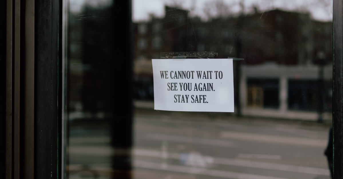 A sign in a business front door ''We cannot wait to see you again. Stay safe.''