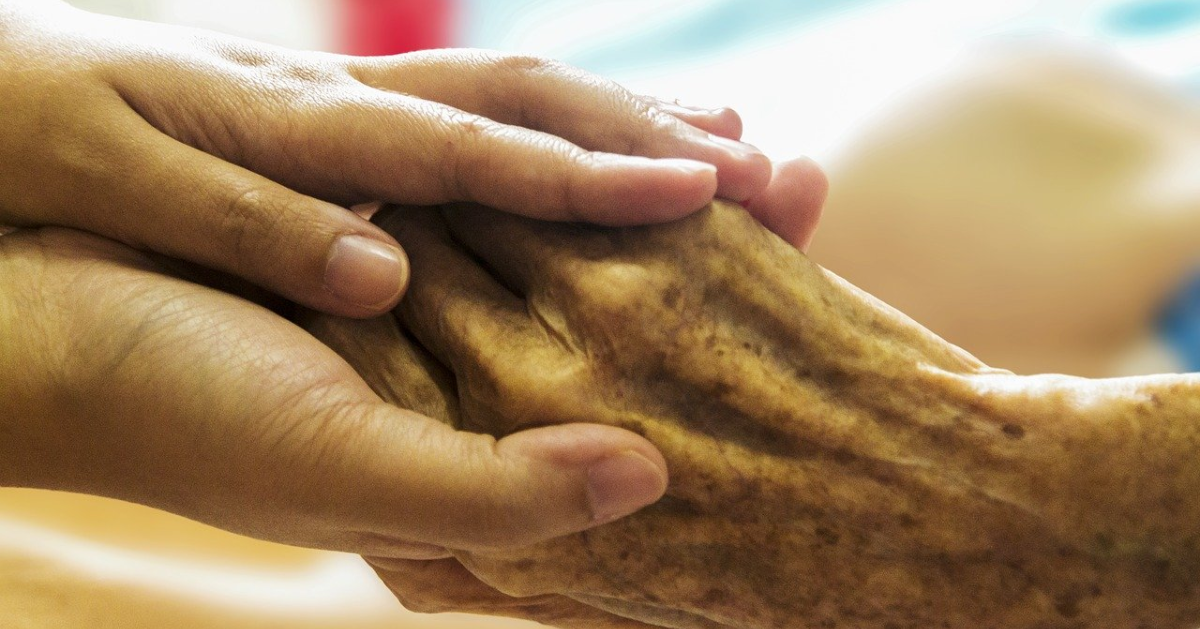 A person holding a senior's hand