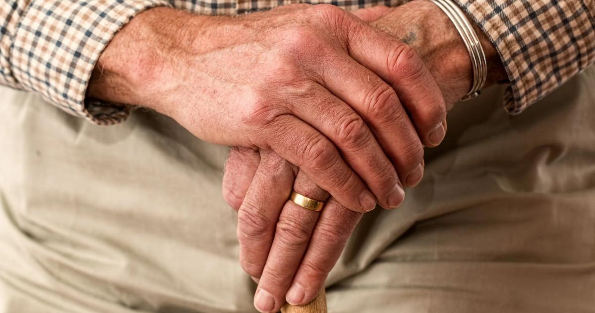 Les mains d'un aîné sur une canne