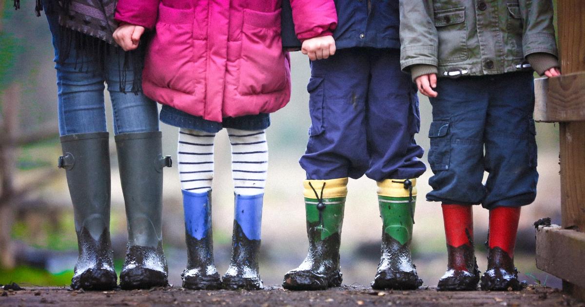 Des jambes d'enfants qui portent des bottes aux pieds