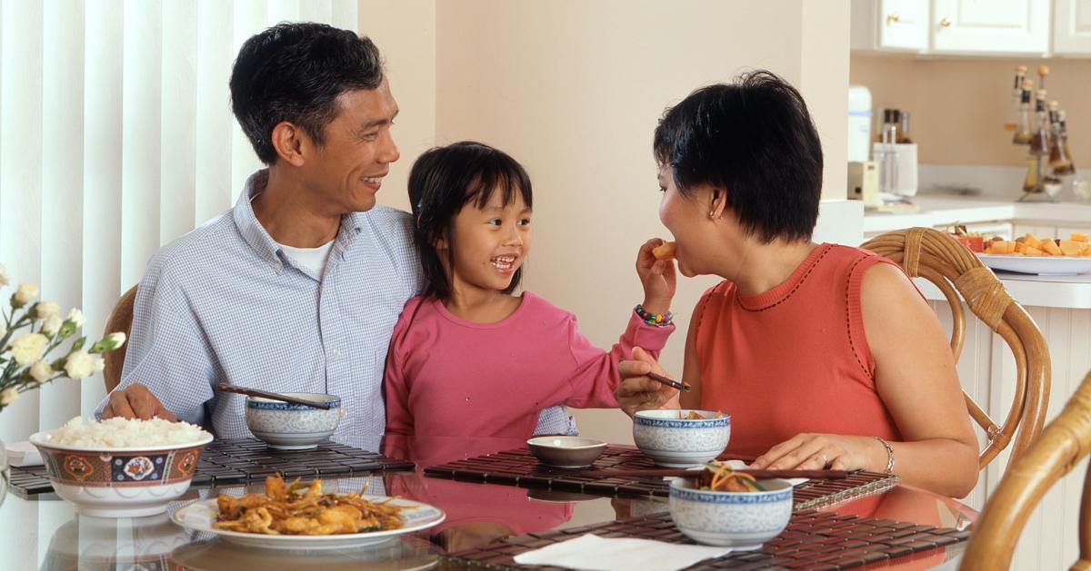 Une famille de trois personnes qui partage un repas