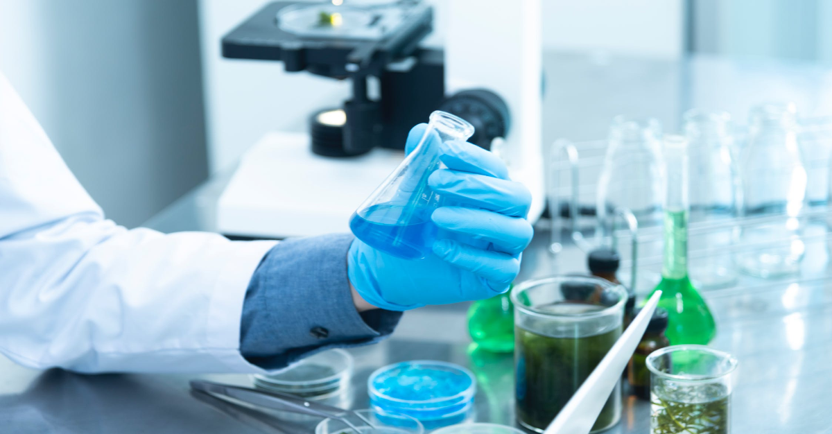 Researcher in lab holding container filled with blue liquid