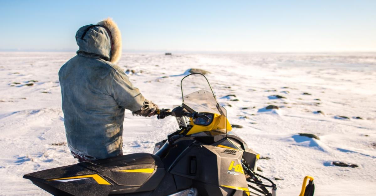 Un Inuit se tenant à côté de sa motoneige en Arctique