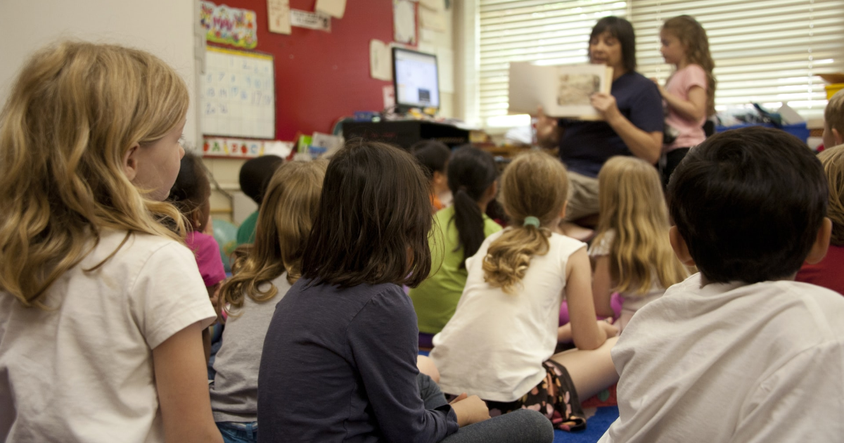 A teacher reading a book to children in a classroom
