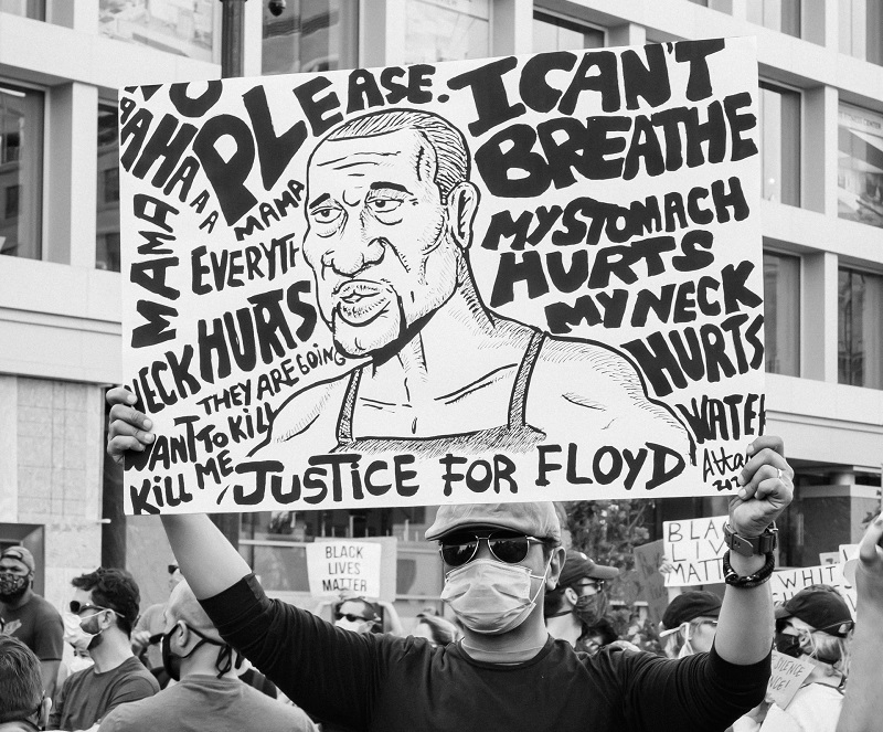 Protester holding sign featuring George Floyd