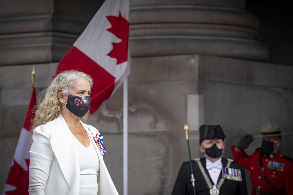 Julie Payette in front of Canada flag
