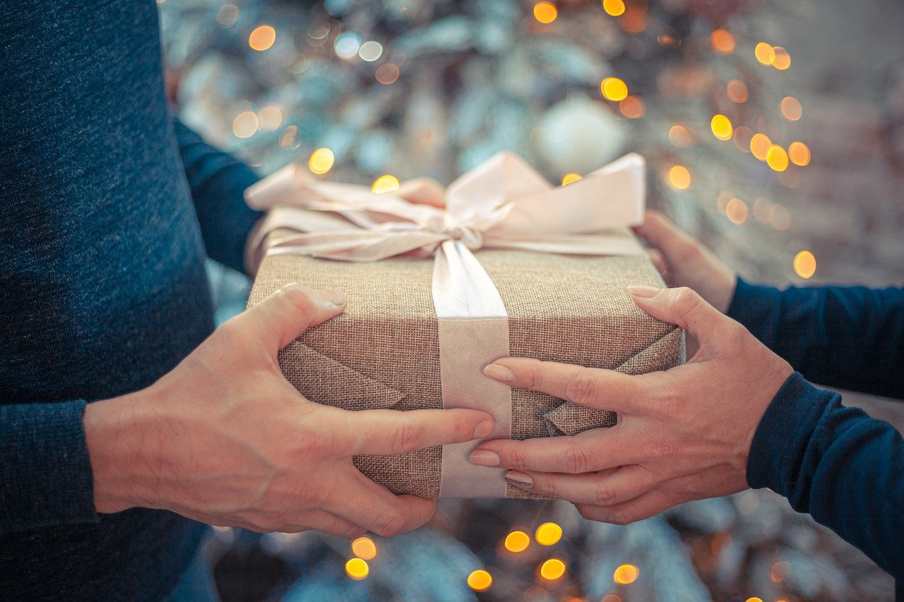 Man and woman's hands shown exchanging gift