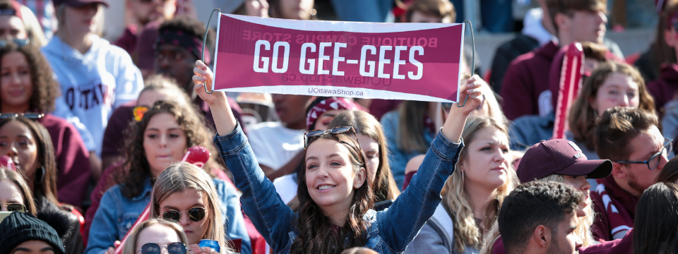 Fan holds up a sign reading 'Go Gee-Gees' at Panda Game