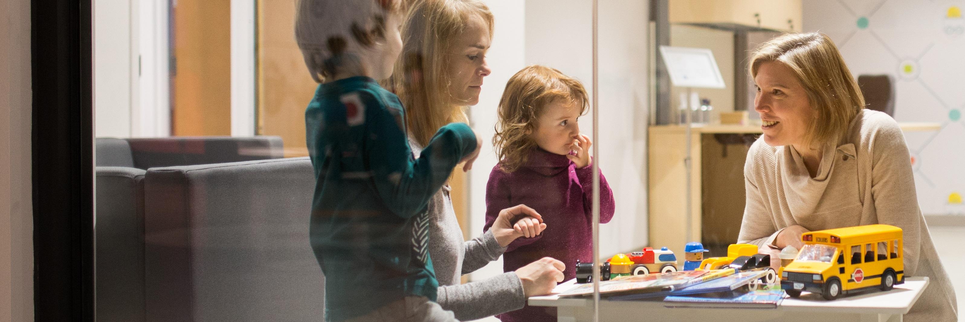 Une chercheure joue à une table avec un jeune garçon et une jeune fille et leur mère.