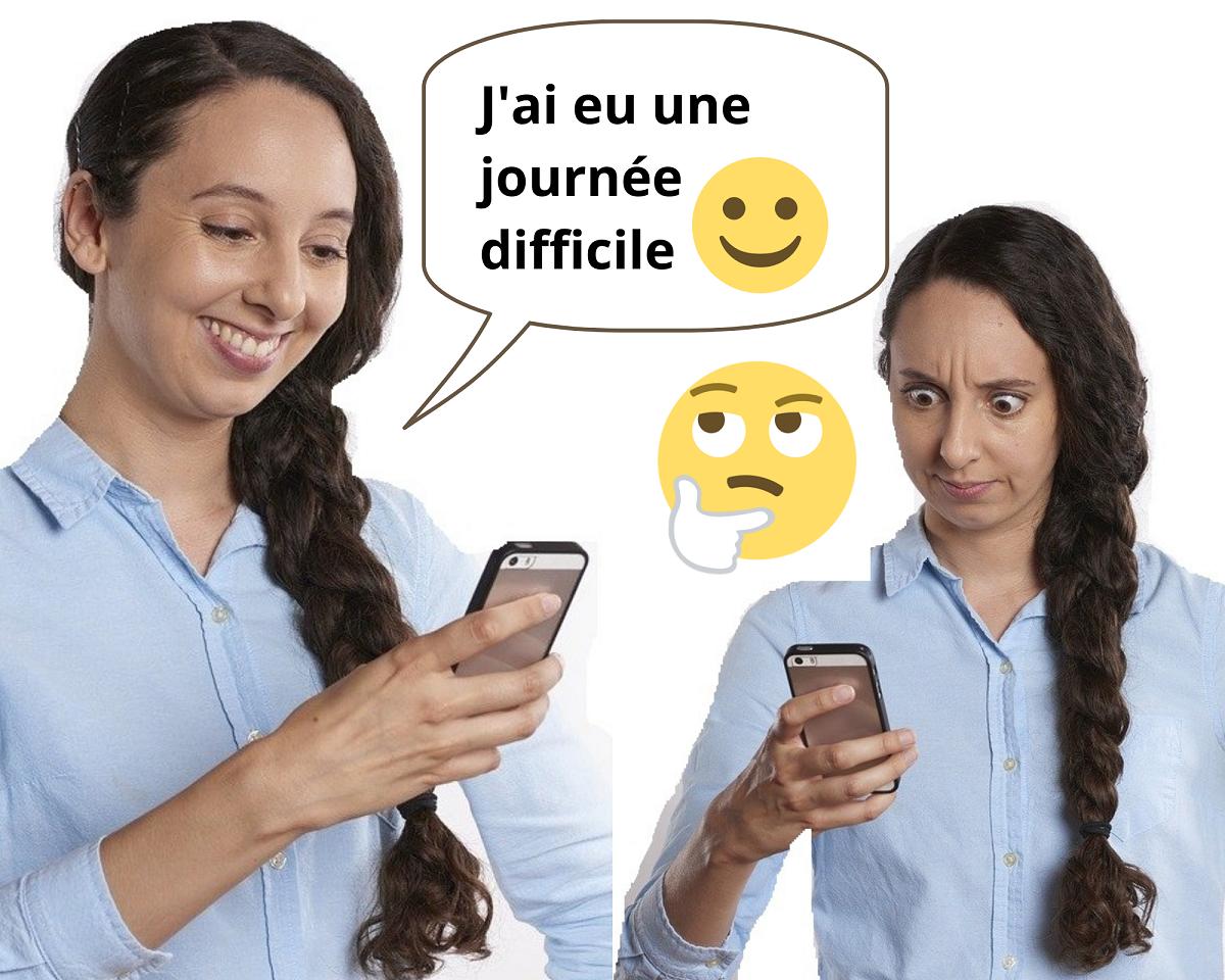 Une femme souriante envoie un SMS négatif avec un émoji positif et la femme qui le reçoit a l'air consternée
