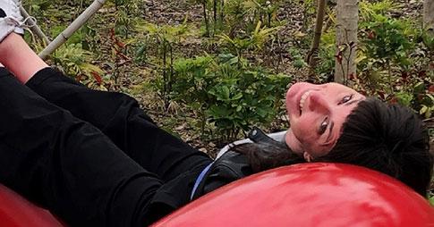 Keri Ryan, souriante, est étendue sur une structure tubulaire rouge vif dans un jardin.