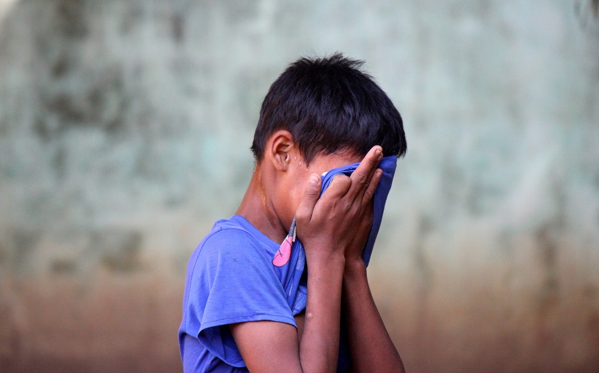 Rohingya boy with head in hands
