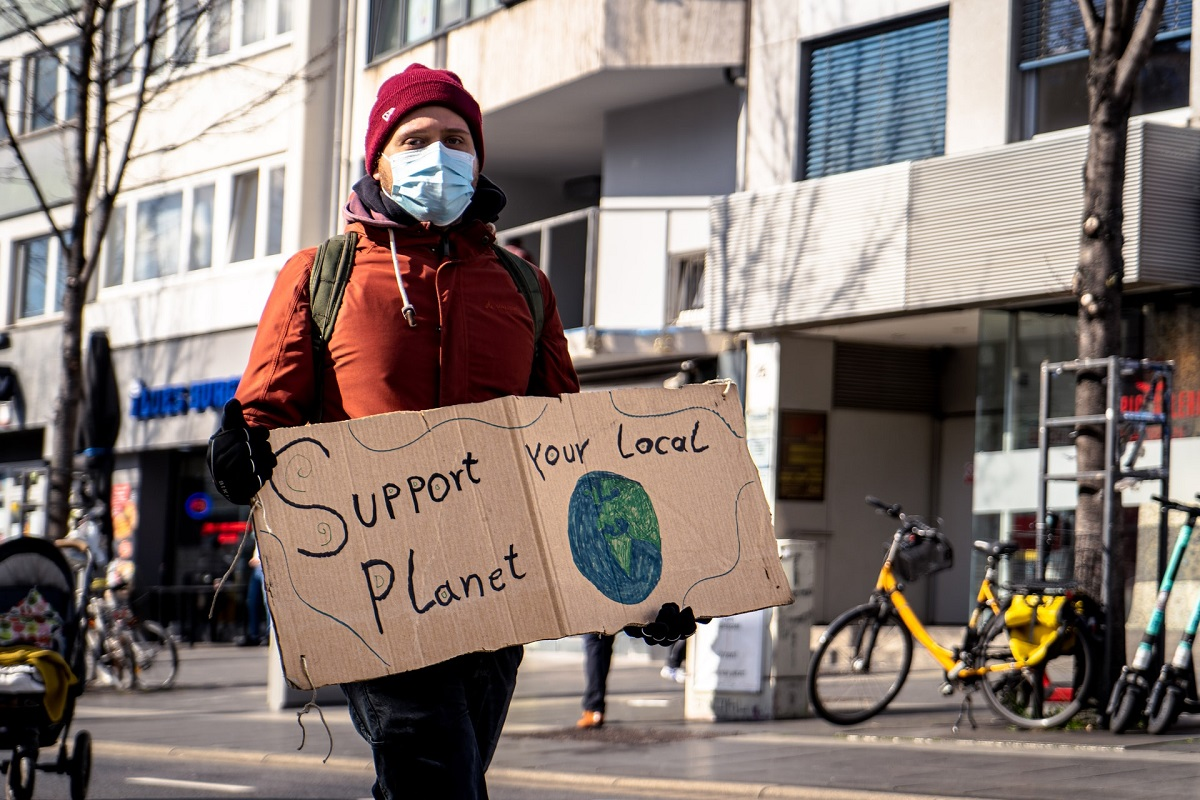 Protestor holding sign reading 'Support your local planet' with drawing of globe on it