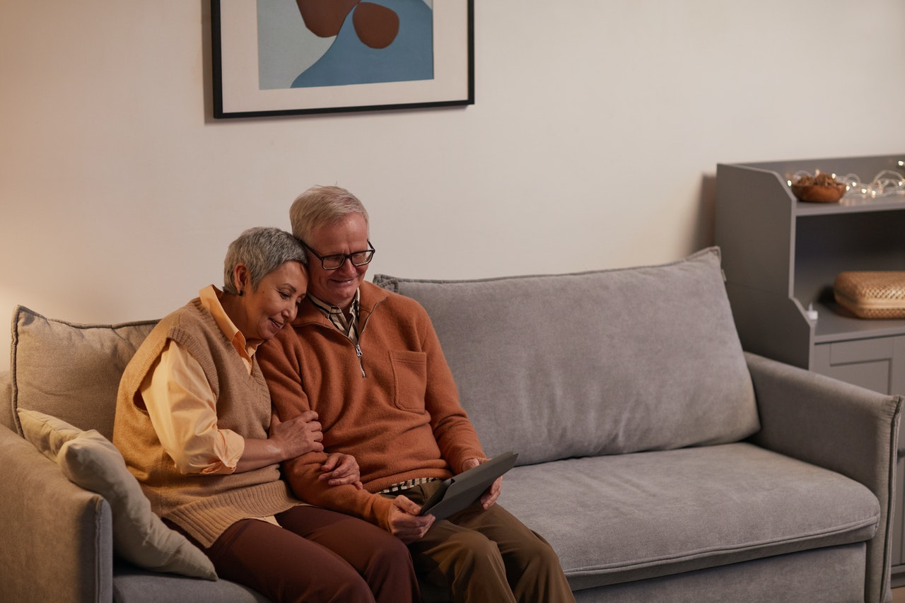 Older couple on couch looking at tablet together