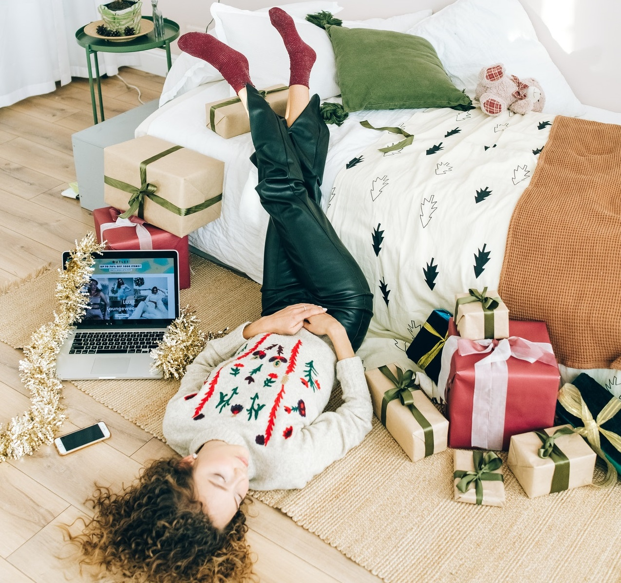 Woman wearing festive sweater alone surrounded by Christmas presents and a computer