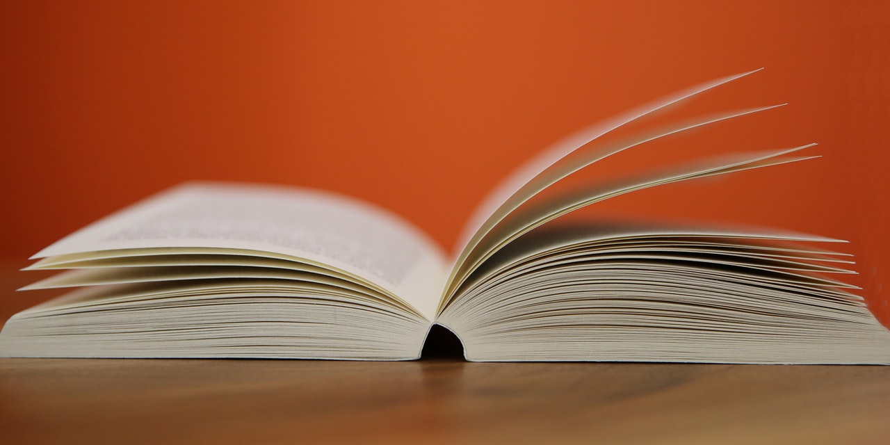 Open book on a wooden table in front of an orange wall