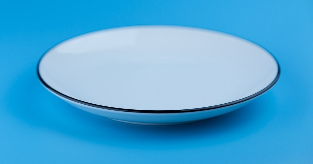 Empty plate on light blue background