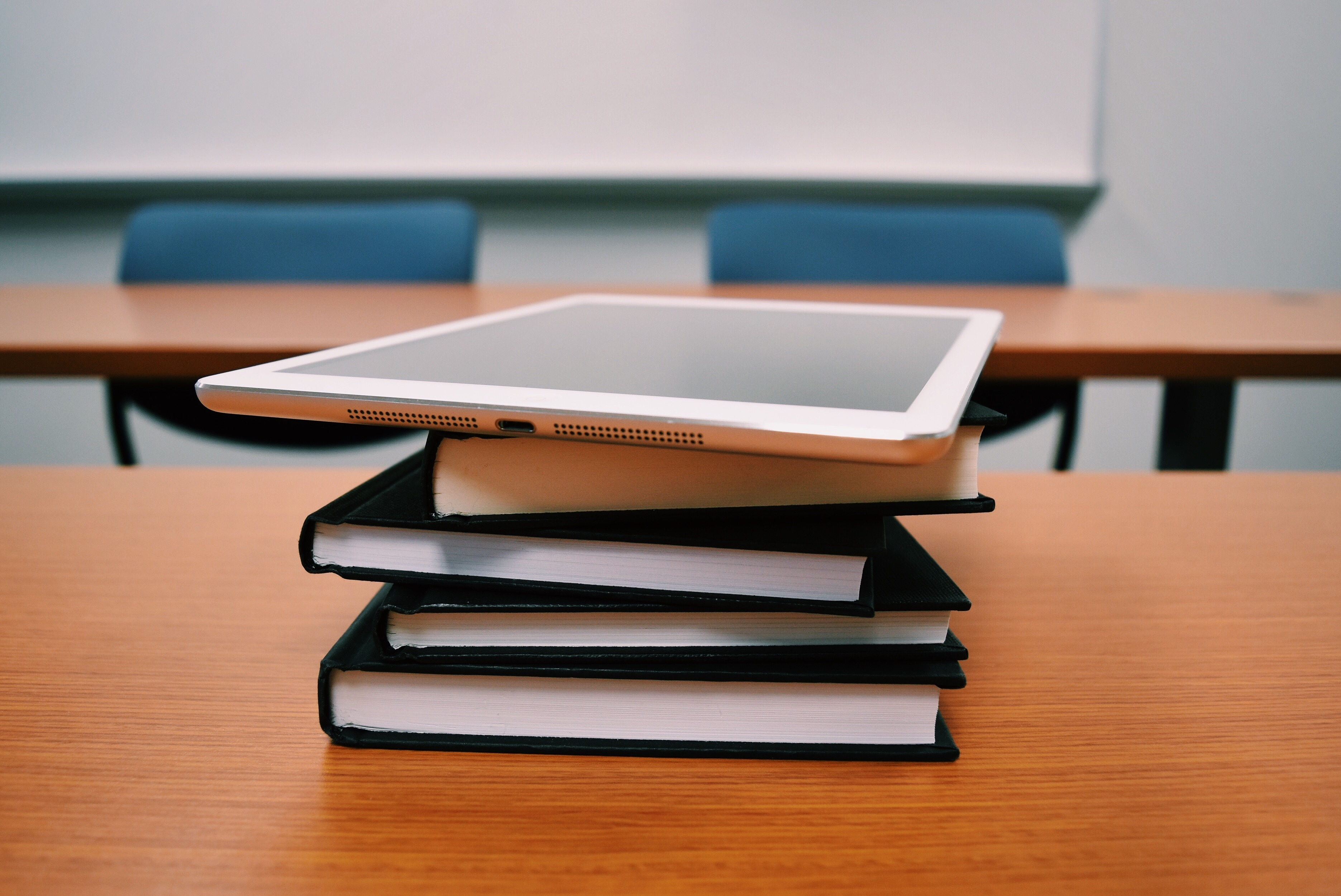 Une pile de livres, sur un bureau avec une tablette numérique au-dessus.