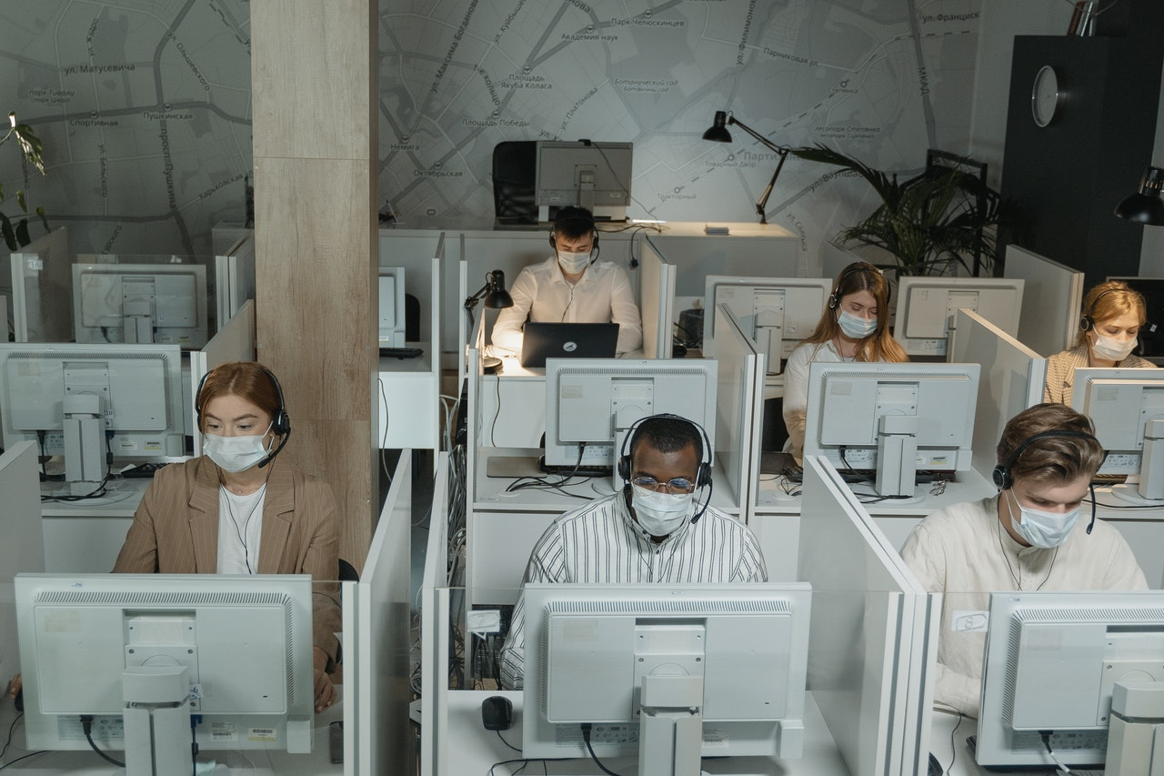 Workers wearing masks sit in crowded cubicles