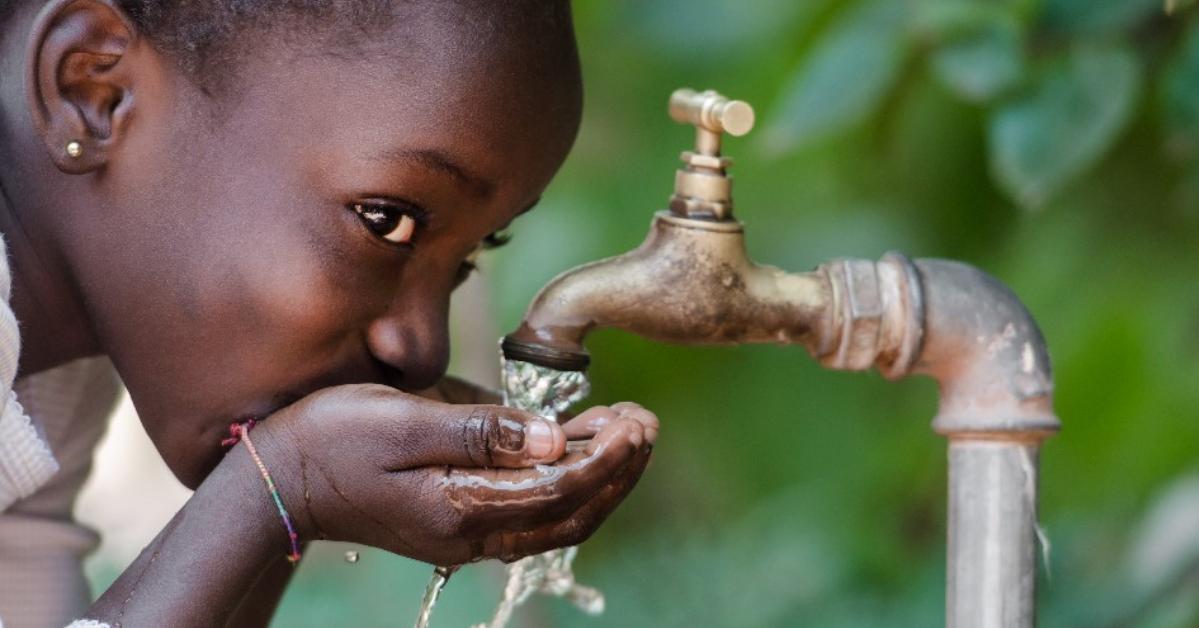 Un enfant qui boit de l'eau d'un robinet