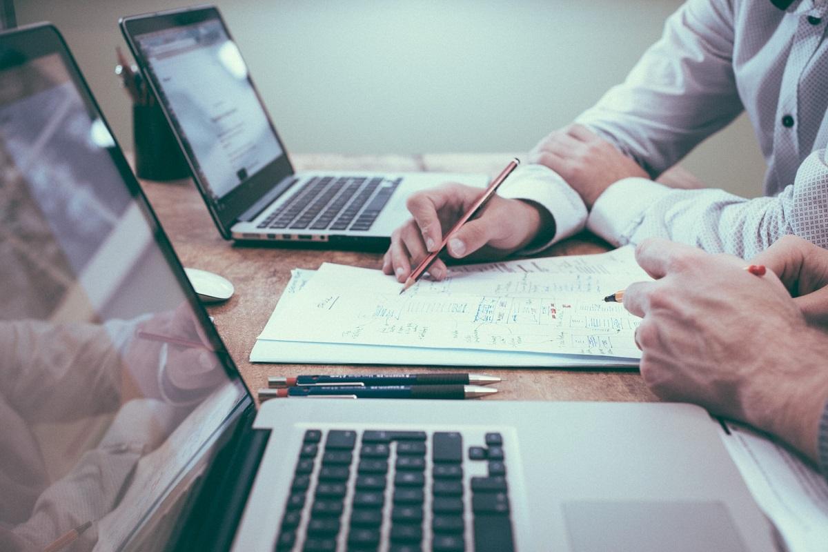 Un homme tient un crayon sur des papiers lors d'une réunion avec un autre