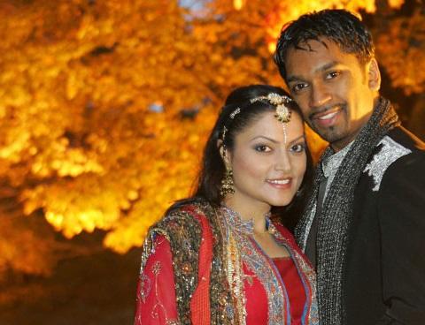 Shawn and Khush Singh, souriant et portant des vêtements traditionnels indiens, se tiennent rapprochés devant un arbre.