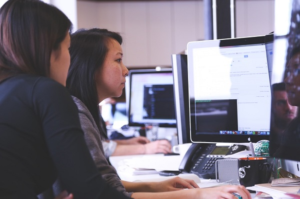 Two young women working on a computer