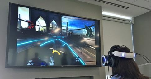 Une personne coiffée d'un casque joue à un jeu vidéo devant un téléviseur.