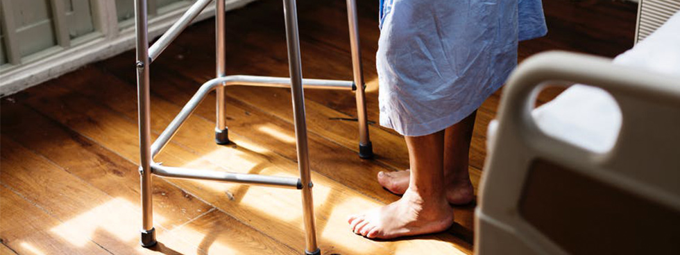 Man wearing a hospital gown shown using a walker